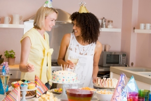 Two women at party standing by food table smiling